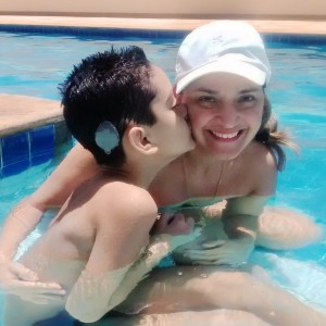 Alexandre and Deborah in pool: supporting a child with hearing loss
