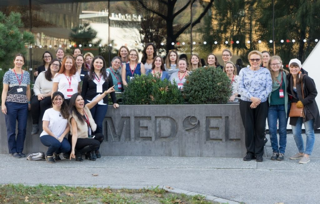 Todos os participantes e organizadores do 1º Meetup MED-EL em frente à matriz, próximos ao logotipo da fachada.