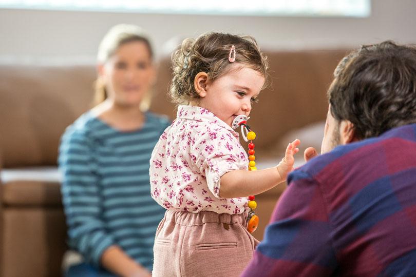 Menina pequena usando implante colcear, interage com o pai agachado à sua frente enquanto é observada pela mãe do outro lado da sala.